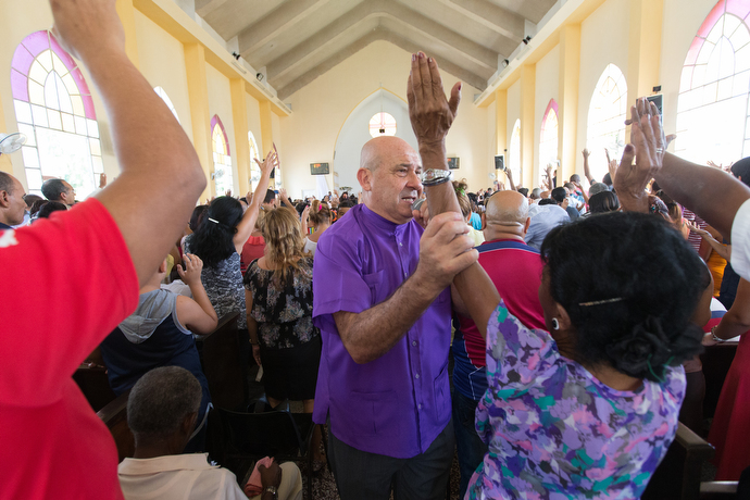 Bishop Ricardo Pereira lays hands on parishioners during worship at Marianao Methodist Church. Photo by Mike DuBose, UMNS.