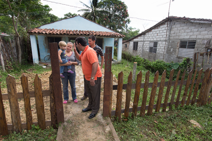 The Rev. Marcio Alcolea offers a high five to Ricardo David, son of pastor  Ricardo Rivero and his wife Ana Maria Torres, who are starting a Methodist church mission at their home. Photo by Mike DuBose, UMNS.