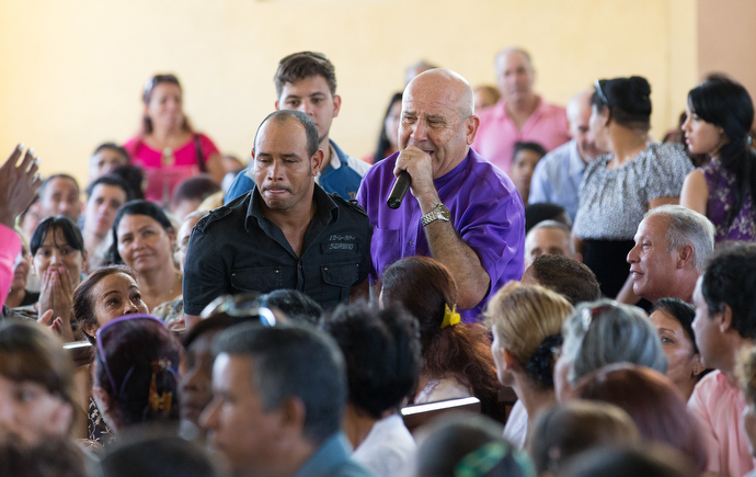 Bishop Ricardo Pereira leads people making a commitment to Christ up the aisle during worship at Marianao Methodist Church in Havana. Photo by Mike DuBose, UMNS.