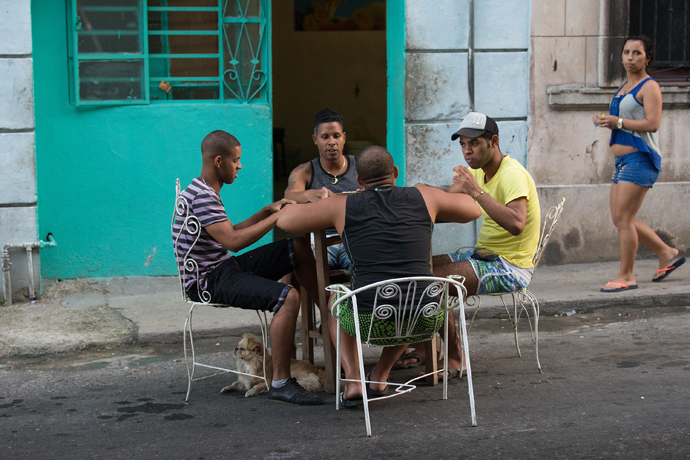 """Friends play dominoes at a table pulled into the street in Havana. """"Life here is very sociable,"""" says Rigoberto Figueroa, — a member of Marianao Methodist Church and vice rector of the Havana seminary. Photo by Mike DuBose, UMNS."""