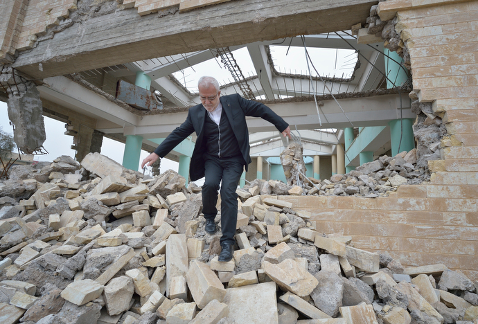Father Emanuel Youkhana walks through the rubble of a church in Mosul, Iraq. The church belonged to the Ancient Church of the East. According to neighbors, the Islamic State group--which took over the city in 2014--used the building as a warehouse until the final weeks of their occupation, when they awarded the building to a contractor who began to demolish it in order to salvage the steel rebar in the walls. Although this portion of the city was liberated in early 2017, Christians are unlikely to return soon due to concerns about their security in the Sunni community. Photo © Paul Jeffrey.