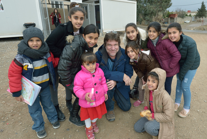 Paul Jeffrey poses with displaced children who participate in a church-run program in the Iraqi village of Bakhtme. Photo courtesy of Paul Jeffrey.