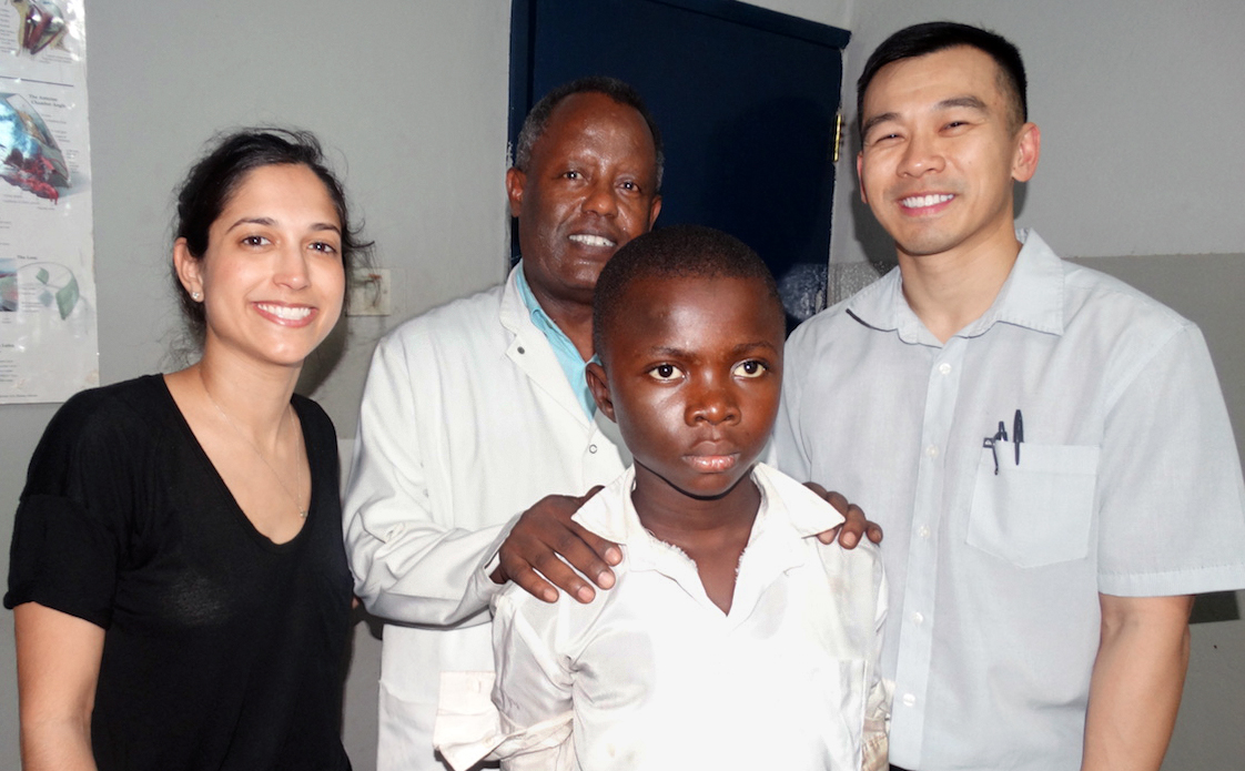Ophthalmologists Jessica Shantha (from left), Moges Teshome and Steven Yeh pose with Umaru Sesay, 12, from Moyamba Junction, Sierra Leone. Sesay, who had cataracts as a result of contracting Ebola, had a successful operation that allowed him return to school. A partnership between Emory University and the Christian Blind Mission provides free cataract surgery to Ebola survivors at the Ruth and Lowell Gess Eye Hospital in eastern Freetown. Photo by Phileas Jusu, UMNS.