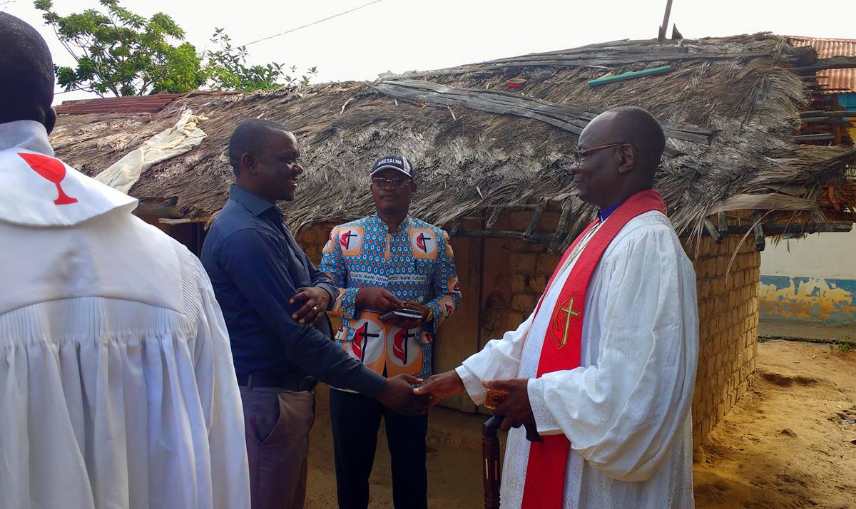 Bishop Gabriel Unda (right) greets Chief Kalema, the chief of Kalima village, as Chief Tunda, a member of the bishop's office, watches. The church, built with contributions from the Rev. Randy Cooper and others in the Memphis Conference, hosted the bishop last year. Photo by Judith Yanga, UMNS.