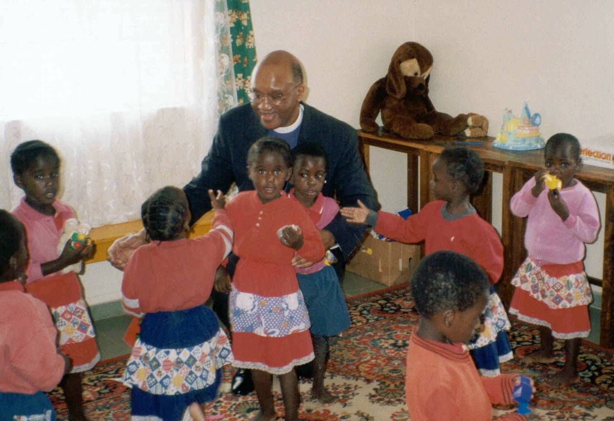"""United Methodist Bishop Felton May plays with children at a Zambian orphanage in 1999 during a trip in support of a Presidential Mission on Children and AIDS.  The trip """"brought me to my knees during Holy Week,"""" said May. May died Feb. 27 at age 81. File photo courtesy of Bishop Felton May."""
