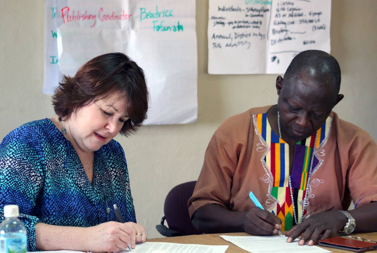 Robin Pippin of Discipleship Ministries, left, and Bishop John K. Yambasu of the Sierra Leone Episcopal Area sign an agreement creating a new publishing team in Sierra Leone. The 12-member team's first project will be the creation of a quarterly newsletter for sharing information about the church with members. Photo by Julu Swen, UMNS