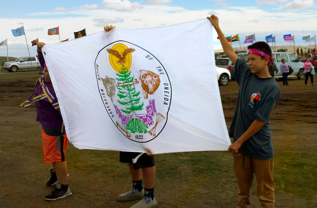 Young people from Oneida United Methodist Church, who attended the Peg-Leg Flamingos youth leadership conference in September, present a tribal flag to water protectors at Standing Rock. Photo courtesy of the Rev. Carol Lakota Eastin