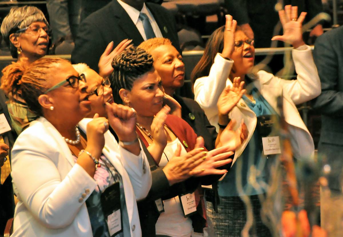 Women raise their hands in praise during the BMCR annual gathering. Caucus members, spanning multiple generations, reveled in worship and fellowship. Photo by John Coleman, UMNS.