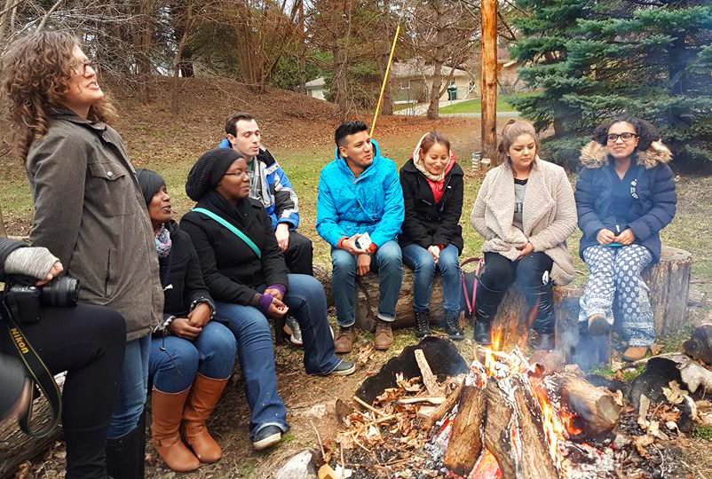 Participants in the 2016 Leadership Training Program in Minneapolis sit around a campfire in the yard of the Fink House, part of the Underground Seminary. The annual training programs are organized by the Student Christian Movement-USA and the World Student Christian Federation-North America. Photo by Luciano Kovacs.