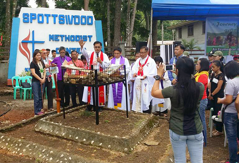 United Methodist Bishop Rodolfo Juan offers a prayer during an interfaith worship service at Spottswood United Methodist Center in Kidapawan City marking the one-year anniversary of an attack on farmers in the Philippines. Photo courtesy of Rodolfo Juan.