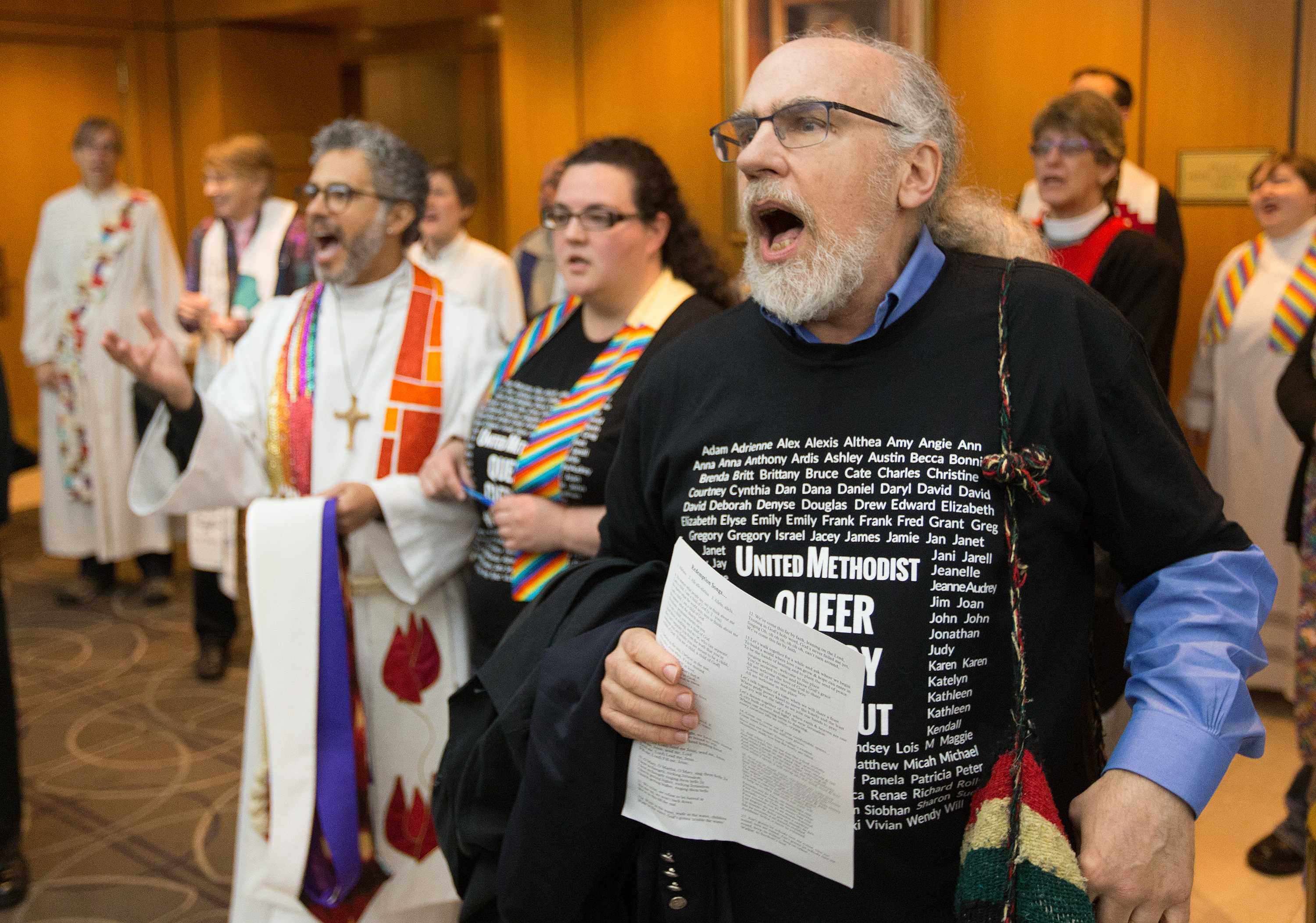 The Rev. K Karpen (right) of St. Paul and St. Andrew United Methodist Church in New York leads a song prior to an oral hearing before the denomination's top court, meeting in Newark, N.J., questioning whether a gay pastor can serve as a bishop in The United Methodist Church. Photo by Mike DuBose, UMNS.