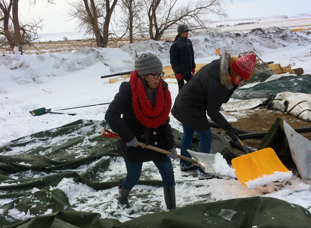 Caitlin Brown, left, a student at Oklahoma City University, and Dr. Leslie Long, right, a professor of religion at OCU, shovel snow at a camp at Standing Rock. The Rev. David Wilson, who has traveled to Standing Rock eight times, accompanied students and faculty from three Oklahoma universities during spring break to help with one of the remaining camps situated on privately owned land near the former Osceti Sakowin camp in North Dakota. Photo by the Rev. Wilson, UMNS.