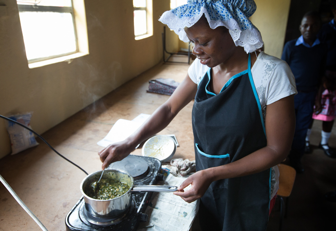 Moreblessing Nagombedze cooks chaya greens, grown on campus, during a meeting of the home management club at Chirichoga High School in Masvingo, Zimbabawe. Photo by Mike DuBose, UMNS.