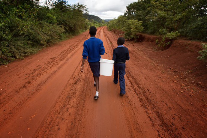 Emelly Maringire, 14, (left) and Malvin Musengwa, 13, walk to fetch water at the end of their school day at Chirichoga High School. Photo by Mike DuBose, UMNS.