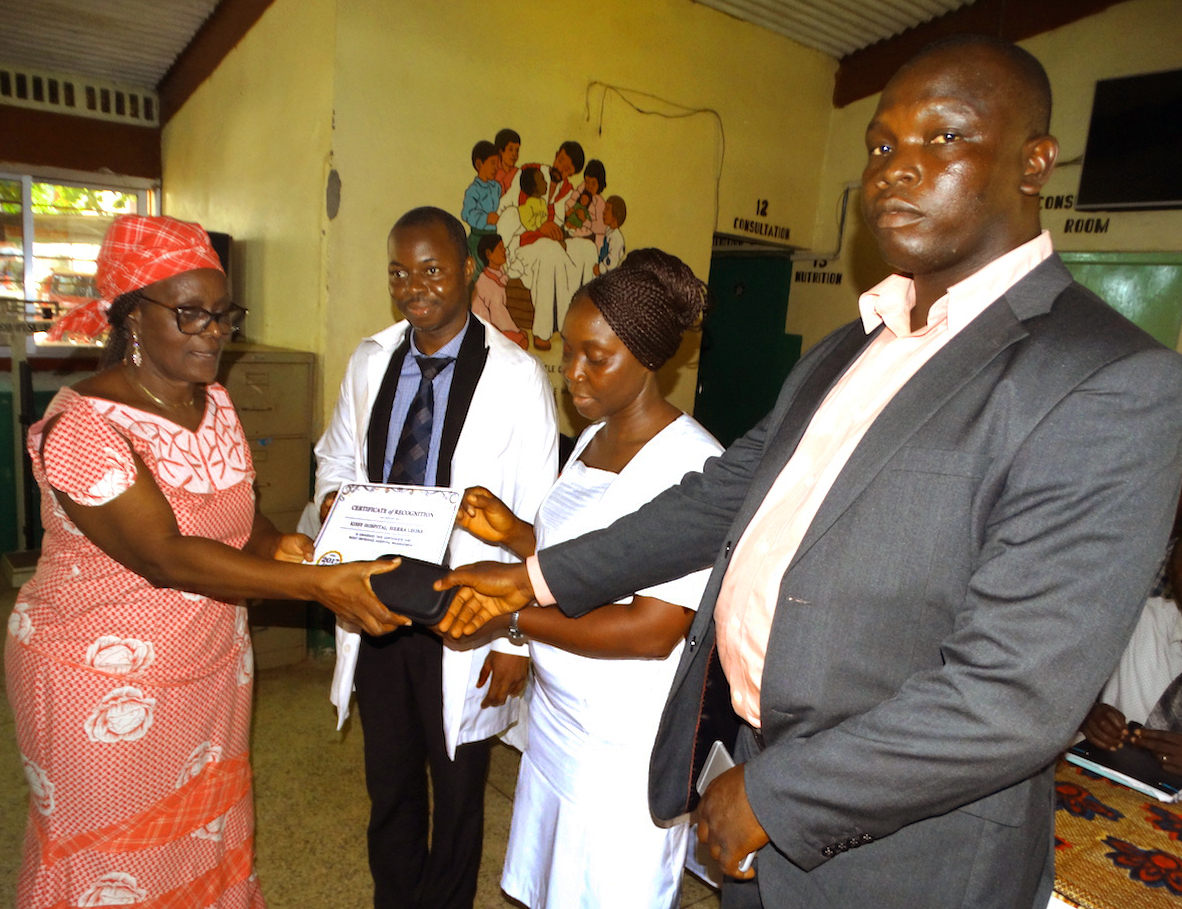 Yeabu Kamara, former chairman of the restructuring committee at Kissy Hospital, hands the certificate of recognition to hospital administrator Joseph Mbogba along with communication gadgets that were part of the award. Photo by Phileas Jusu, UMNS