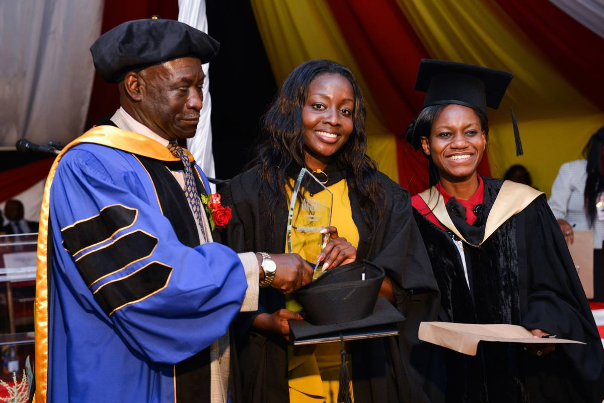 Class valedictorian Kudakwashe Mellisa Kapesa (center) holds a trophy honoring her scholastic achievements during the 2017 commencement ceremonies at Africa University in Mutare, Zimbabwe. Kapesa, who had a cumulative GPA of 3.92, is flanked by the Deputy Vice Chancellor Pro Deputy Vice Chancellor, Professor Ikubolajeh Logan (left) and the Acting Registrar, Miss Tafadzwa Mushambi (right). Photo courtesy of Africa University.