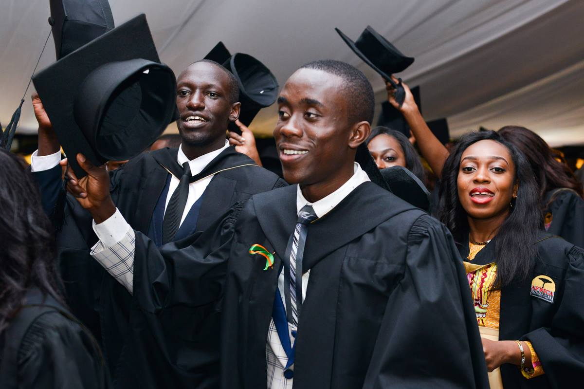 Odilon Mwaba (center) and Tikky Giorgio Olang'o (left) raise their caps in celebration at Africa University's 2017 commencement. More than 700 students from 23 African countries graduated from the United Methodist university in Mutare, Zimbabwe. Photo courtesy of Africa University.