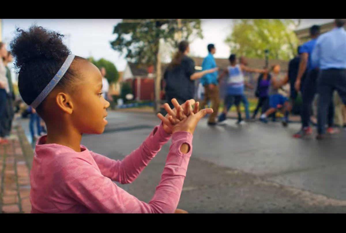 """In Discipleship Ministries' video introducing the """"See All the People"""" initiative, a girl plays the nursery rhyme game of that name, as the pastor and several staff members of a church join in a basketball game with neighborhood children. Video image courtesy of Discipleship Ministries."""