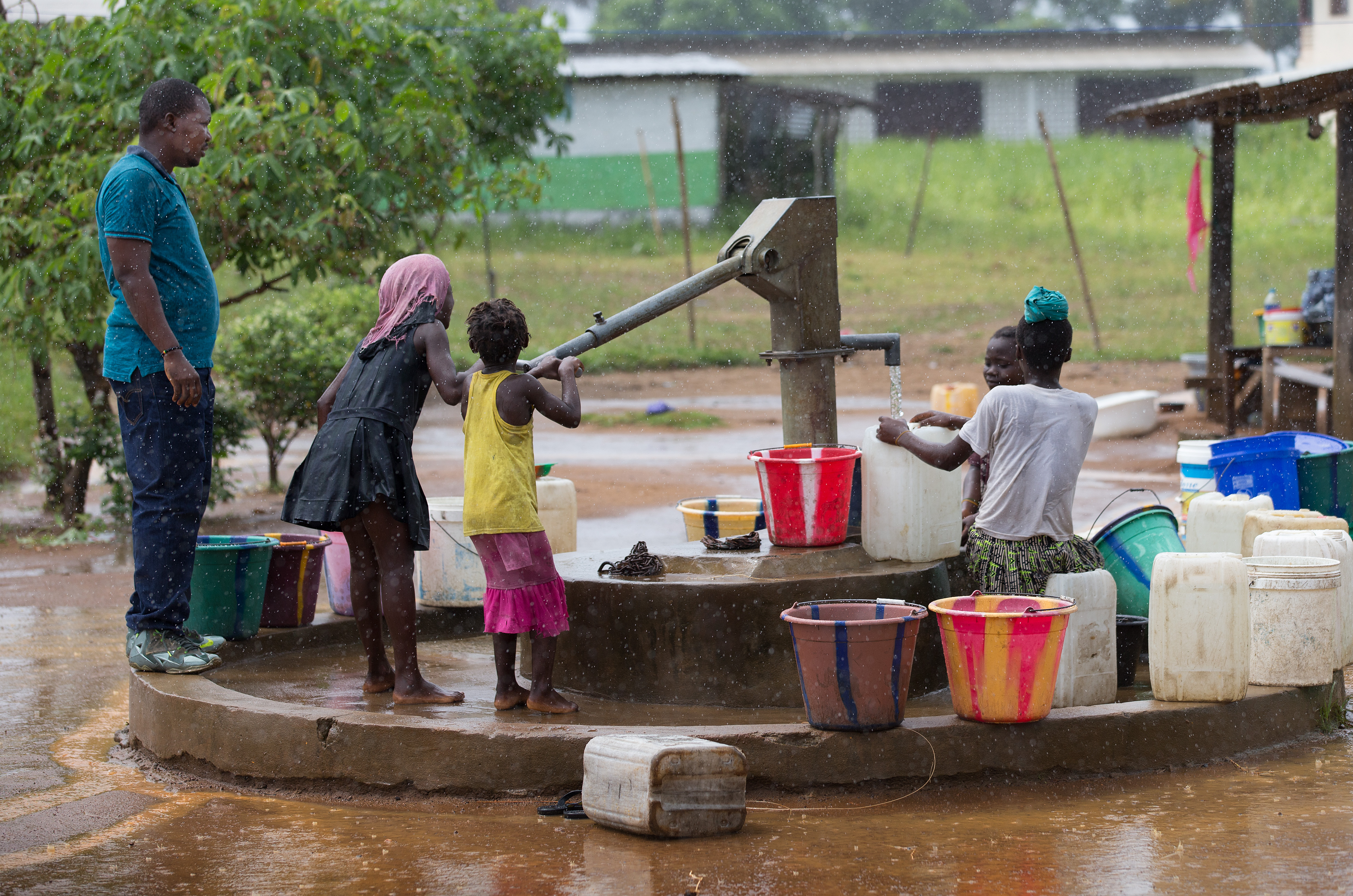Jefferson B. Knight (left) checks on the output of a water well during the rainy season in Robert's Town Village near Marshall City, Liberia. Knight is director of the Peace With Justice Program for the United Methodist Liberia Conference. Photo by Mike DuBose, UMNS.