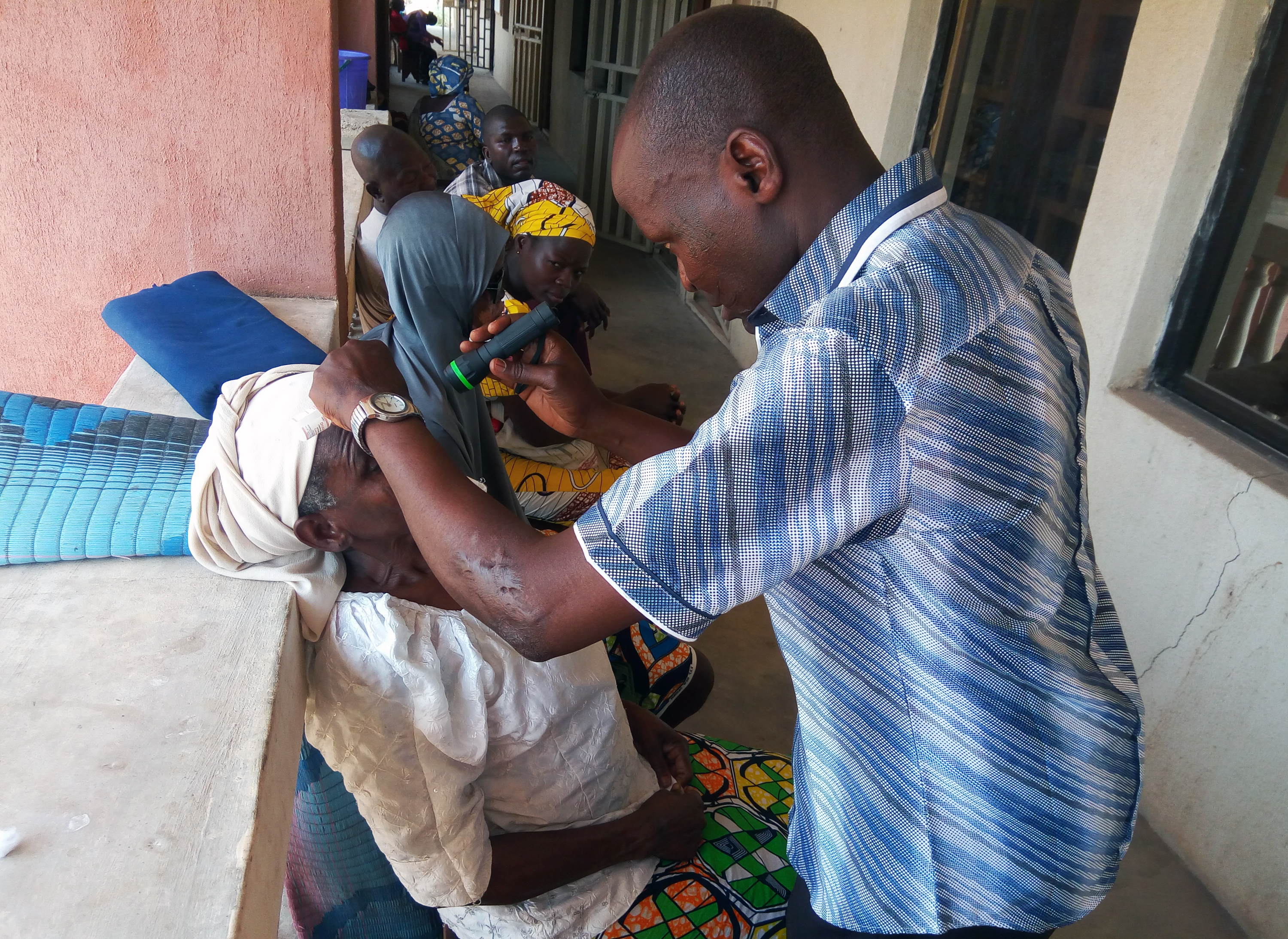 A woman has her eyes examined by a medical attendant while other patients sit waiting in line at Gwandum Clinic in Nigeria. Photo by the Rev. Ande I. Emmanuel, UMNS.