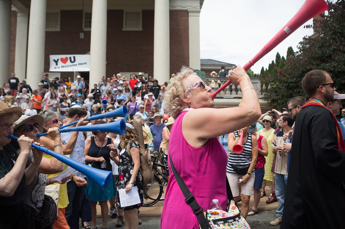 The Rev. Seth Wispelwey (right), co-moderator of Sojourners United Church of Christ in Charlottesville, Va., leads a group headed to oppose a KKK Rally there, as the Rev. Elaine Ellis Thomas, associate rector and chaplain, St. Paul's Memorial Episcopal Church (second from right) blows a vuvuzela. Behind them is First United Methodist Church, where the Charlottesville Clergy Collective had arranged a gathering. An estimated 1,000 were on hand to protest the rally. Photo by Michael Cheuk.