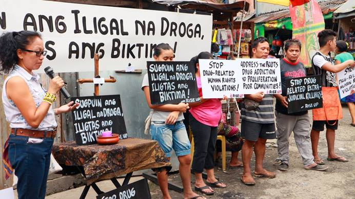 "In a file photo from December 2016, Norma Dollaga, on left with microphone, speaks during an ecumenical action of Kadamay: Stop the Killings, a community organization that advocates for the poor in urban communities, in Quezon City, Philippines. The placards in Filipino say, ""Dismantle illegal drugs, Save the victims!"" Photo courtesy of Norma Dollaga."
