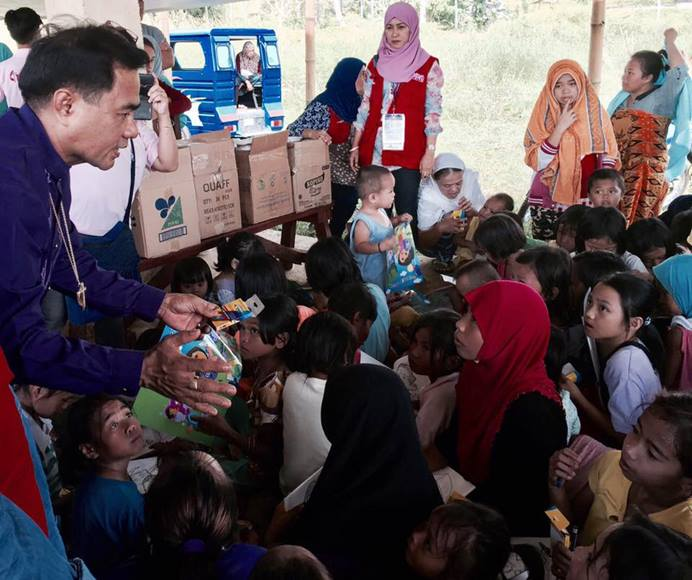 Bishop Rodolfo A. Juan (left) hands out crayons to children who fled with their families to escape fighting between government forces and Islamic State militants on the island of Mindanao in the Philippines. The families are staying at an evacuation center in Bito-Buadi, Marawi City, where United Methodists are helping those displaced. Photo by the Rev. Israel M Painit