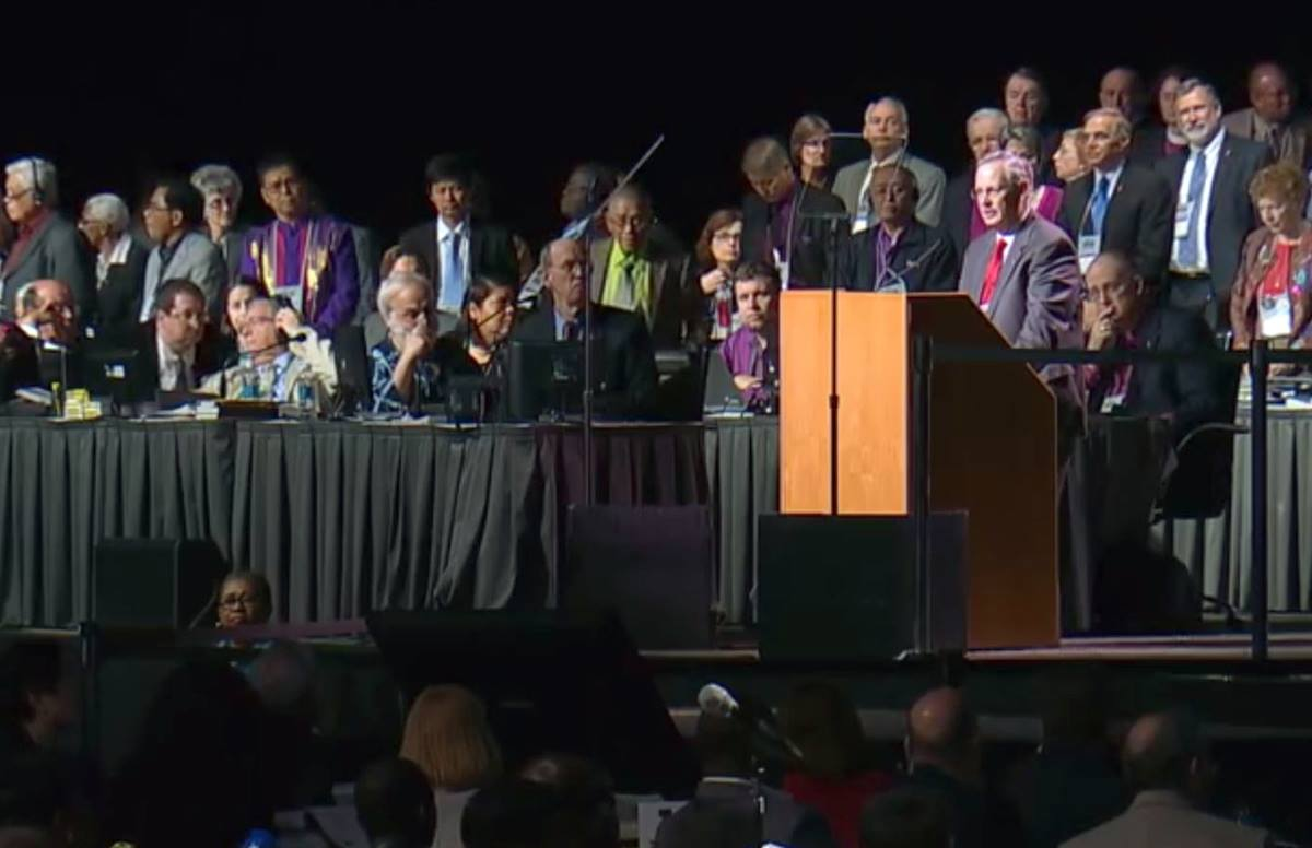 In a video file image, Bishop Bruce R. Ough, at podium, delivers a statement from the Council of Bishops about the formation of the Commission on a Way Forward during the 2016 General Conference in Portland, Ore. Video image courtesy of United Methodist Communications.