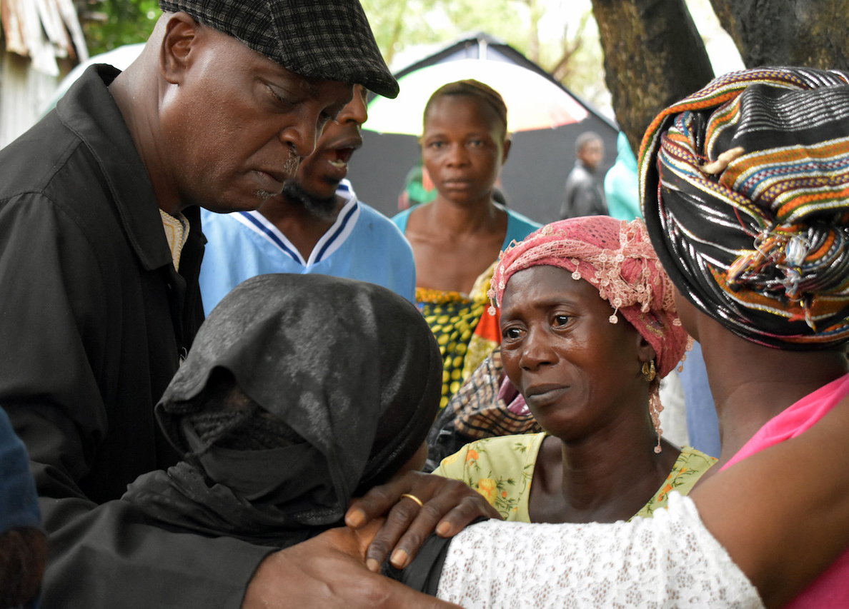 The Rev. Henry Samuel of Vine Memorial Baptist Church, an affiliate member of the Council of Churches in Sierra Leone, prays with and consoles a group of women who lost 17 members of their family during the Aug. 14 flood and landslide in in Freetown. Photo by Phileas Jusu, UMNS.