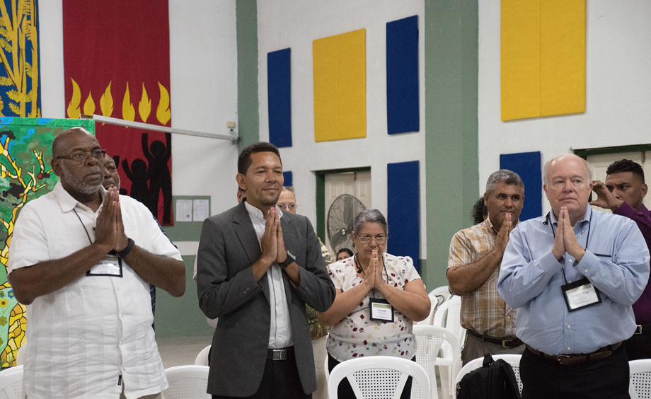 (From left) Bishop Jonathan Holston, the Rev. Carlos Cornejo, Claudete Mora, the Rev. Luis Soto and Bishop Mike McKee use body movement to pray the Lord's Prayer as part of a devotion given by Bishop Cynthia Moore-Koikoi, at Cristo Resucitado, Ciudad España, Honduras.