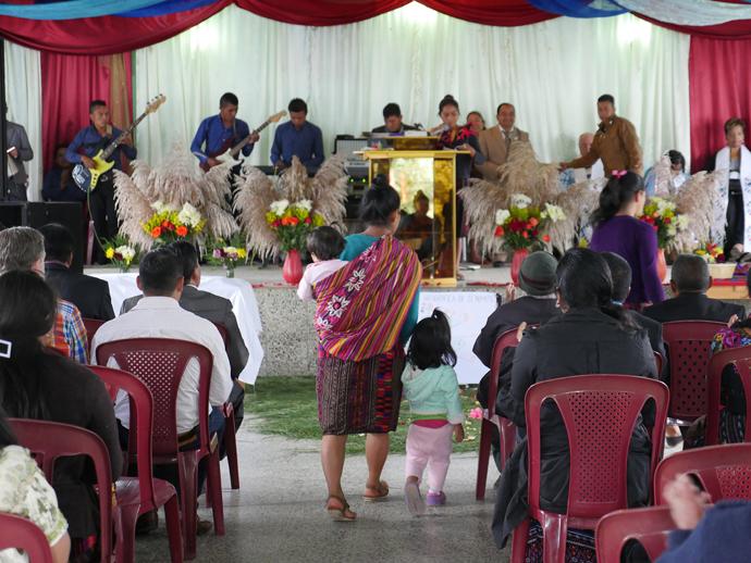 An usher with her two small children prepares to take an offering at Iglesia Nacional Methodista Fuente De Vida, Guatemala.