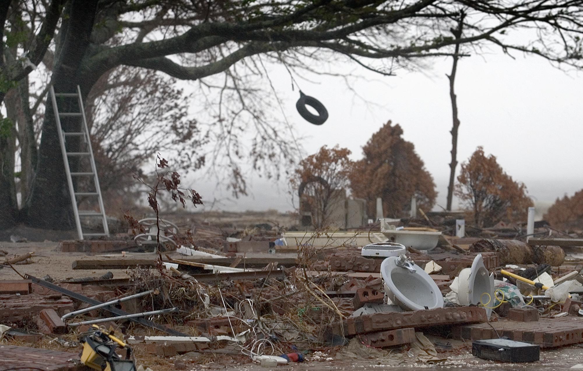 Un neumático se balancea por el viento del huracán Rita sobre los restos de una casa frente al mar, destruida por el huracán Katrina en Ocean Springs, Mississippi. Rita tocó tierra al este de Texas el 24 de septiembre de 2005, casi cuatro semanas después de que Katrina azotara Louisiana y Mississippi. Foto de Mike DuBose, Noticias MU.