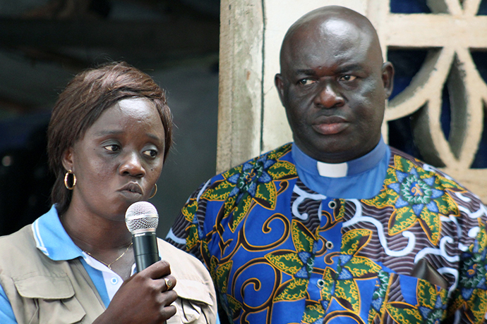 Catherine Norman (left), Sierra Leone Conference health coordinator, speaks at a relief station in Freetown, Sierra Leone. The Rev. James Boye-Caulker (right), superintendent of Western District of The United Methodist Church in Sierra Leone, prayed before food was distributed. Photo by Julu Swen, UMNS.