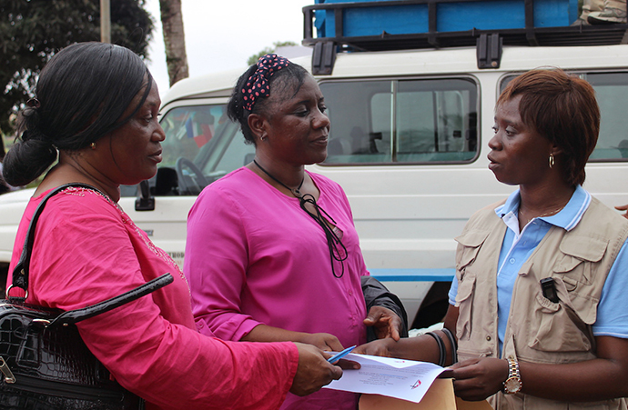 Sierra Leone Annual Conference Health Coordinator Catherine Norman (right) confers with government health representatives at one of the relocation centers where people displaced by the Aug. 14 disaster can seek help. Photo by Julu Swen, UMNS.