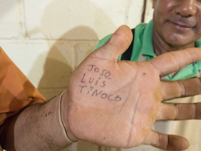 It is loud inside the cigar factory, Jose Luis Tinoco found it easier to write his name on his hand for the visiting reporter. Tinoco and Santos Martinez work in the fermentation process, they rehydrate each leaf using a rubber hose in a small humid cinder-block room. Photo by Kathy L. Gilbert, UMNS.