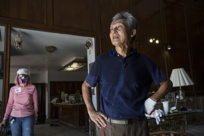 An emotional Dan Cho describes the extensive flood damage to his Houston home as Anne Thomas, of the city's Chapelwood United Methodist Church, stands by. Chapelwood has had teams mucking out homes flooded in the aftermath of Hurricane Harvey, and Thomas was part of a team working at Cho's on Sept. 11. Photo by Kathleen Barry, UMNS.