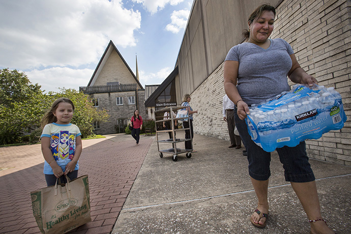Four-year-old Joely Salguero and Marty Pineda carry supplies distributed by Houston's Westbury United Methodsit Church to flood victims of Hurricane Harvey. Photo by Kathleen Barry, UMNS.