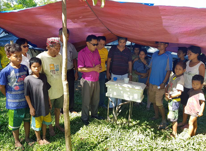 Bishop Rodolfo A. Juan (center in pink shirt) prays with the bereaved family of a baby who was born — and died — at a refugee camp in Malaybalay, Philippines. The camp in northern Mindanao was set up after an outbreak of violence against Lumads (indigenous peoples). Photo courtesy of Dan Ela.