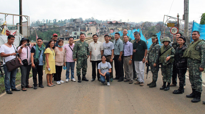 A United Methodist mission team stands at the Mapandi Bridge where the fiercest battle between government troops and the Maute happened. Photo courtesy of the Rev. Capt. Eduardo Copliting.
