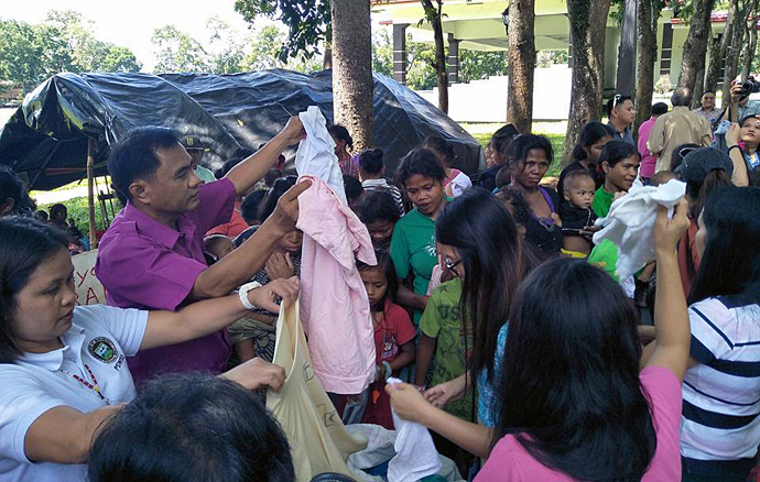 Articles of clothing are among relief items distributed by United Methodists, including Bishop Rodolfo A. Juan (second from left), to Lumads fleeing violent conflicts in the Philippines. The bulk of the items were donated by Korean churches. In the background stands the tent where the Lumads are camping out near the capitol grounds in Malaybalay. Photo courtesy of Dan Ela.