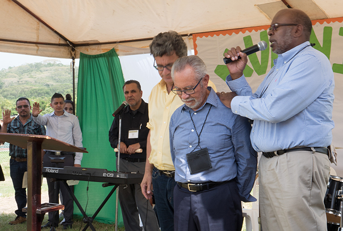 (center) Bishop Elias Galvan, director of the Honduras Mission Initiative, receives prayers and blessings from Bishop Jonathan Holston, South Carolina Area (right) and Thomas Kemper, top executive of the United Methodist Board of Global Ministries (left). The Rev. Edgar Avitia Legarda, Global Area Liaison with the Board of Global Ministries (back left), translates. Photo by Kathy L. Gilbert, UMNS.