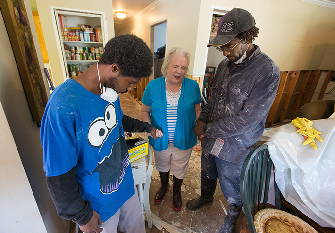 The Rev. Susan Ferguson (center) of Asbury United Methodist Church in Lafayette, La., prays with Trent Noel (right) and his son, Jay Barnes, who were gutting flood-damaged drywall at the home of Noel's mother in August 2016. File photo by Mike DuBose, UMNS