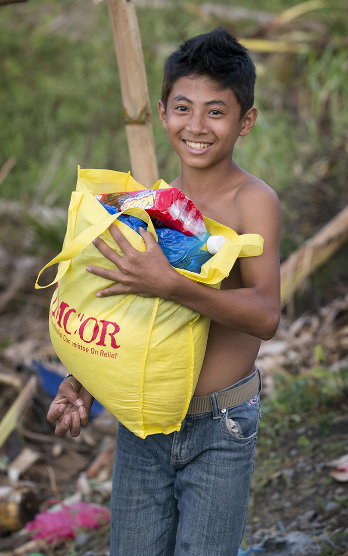 A young boy leaves a food distribution center set up by the United Methodist Committee on Relief carrying food for his family following Typhoon Haiyan in Dagami, Philippines, in 2013. Photo by Mike DuBose, UMNS.