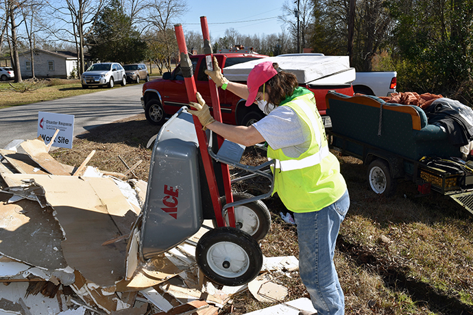 A woman uses a wheelbarrow to remove debris on a United Methodist disaster response site in South Carolina after Hurricane Matthew in 2016. Photo courtesy of the South Carolina Conference of The United Methodist Church.