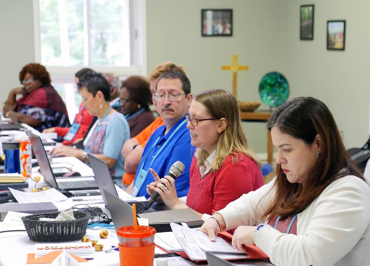 Sara Hotchkiss, in red, speaks during the Commission on General Conference meeting Oct. 7 at Camp Sumatanga in Gallant, Ala. Earlier in the meeting, Hotchkiss helped explain plans for the special General Conference in 2019. Photo by Heather Hahn, UMNS.