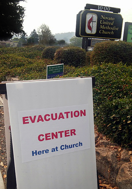 An evacuation sign posted by Novato United Methodist Church in Novato, California, shows the way for those seeking shelter after deadly wildfires broke out across the state, Oct. 9. The church hosted about 60 people during the day on Monday and 50 overnight. Photo courtesy of Novato United Methodist Church.