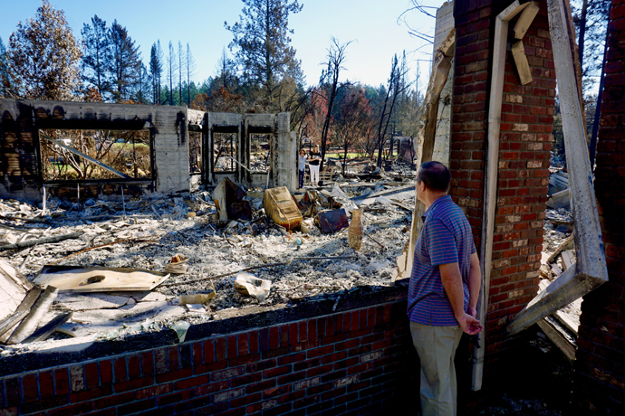 The Rev. Blake Busick looks through an opening at his house at rubble and singed trees after wildfires swept through his neighborhood in Santa Rosa, California. Photo by Sue Larson, courtesy of the Rev. Blake Busick.