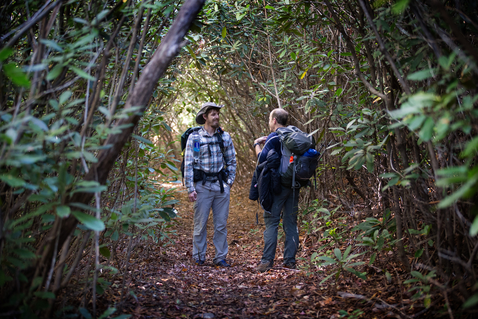 The Rev. Matt Hall (left) visits with a fellow hiker inside a rhododendron grove along the Appalachian Trail near Bland, Va.