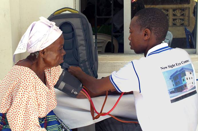 A staff member of the New Sight Eye Center in Liberia checks vitals on one of the senior citizens who benefited from free clinical health services provided by The United Methodist Church's Aging Ministry. The clinic was part of the activities for Senior Citizens Sunday sponsored by the Liberia Conference, and benefitted hundreds of seniors. Photo by Julu Swen, UMNS.