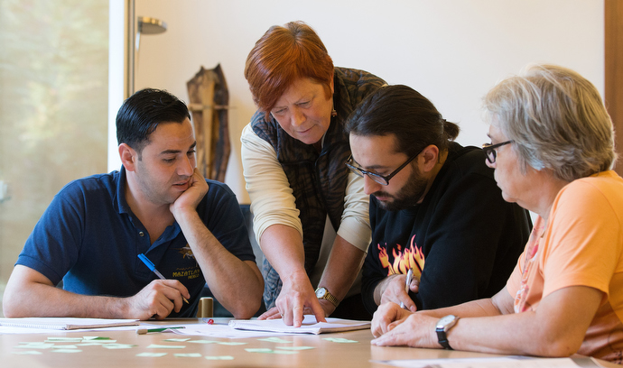 Uta Dauner Eisbrenner helps Muhammad Mshehadat (left) and Maker Araksousi with a vocabulary exercise during a German class for recent immigrants at the United Methodist Church of the Caller in Frankfurt, Germany. Helping, at right is volunteer Christa Shweitzer.  Photo by Mike DuBose, UMNS.